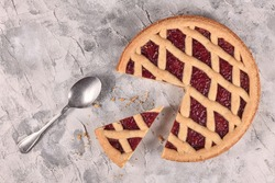 Whole pie called 'Linzer Torte', a traditional Austrian shortcake pastry topped with fruit preserves and sliced nuts with lattice design with slice cut out