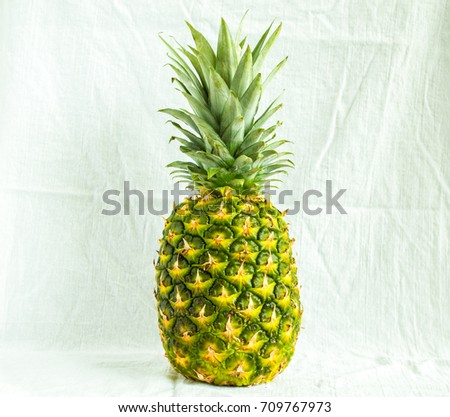 Photo of whole pineapple isolated on a white cloth