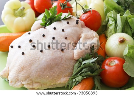 Whole raw chicken with vegetables and pepper