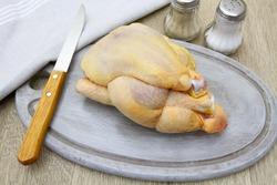 whole raw guinea fowl on a cutting board