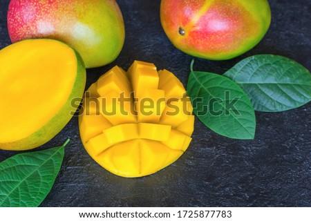 whole ripe mangoes and mango halves close-up. fresh ripe mangoes on a wooden background. mango close-up.