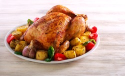 Whole roast spicy chicken with potatoes, on plate over wooden background