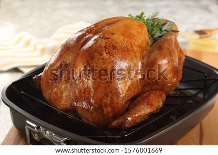 Whole roast turkey in black roasting pan. #1576801669