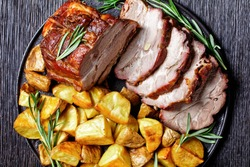 Whole roasted pork loin served with baked potato wedges, rosemary  on a black plate on a dark wooden background, top view, close up