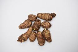 Whole Taro root or Colocasia esculenta raw root vegetable also known as Arbi in India on white background. Tasy Saudi arabian, Pakistani, Indian, Bangladeshi, Srilankan root vegetable.