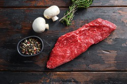 Whole tri tip steak with fresh seasoningsm thyme, organic tri-tip roast with fat marbled through the meat ready to roast or barbecue on rustic wooden background, top view
