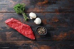 Whole tri tip steak with fresh seasoningsm thyme, organic tri-tip roast with fat marbled through the meat ready to roast or barbecue on rustic wooden background, top view space for text.