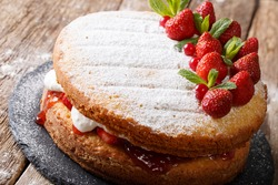 whole Victoria sandwich cake, decorated with strawberries, cranberries and mint closeup on the table. horizontal