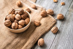 Whole walnuts in a bowl and jute bag on rustic old wooden table. Healthy organic food, BIO viands, natural background. Copy space for your advertising text message.