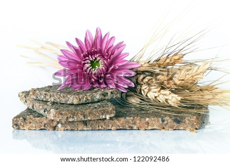 whole wheat bread with ears of wheat and pink flower on a white background
