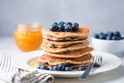 Whole wheat pancakes with blueberries and honey on a plate. Tasty breakfast food, stack of homemade pancakes