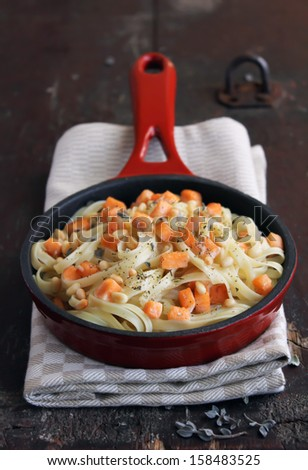 Whole wheat pasta with roasted salmon and cream sauce in a pan