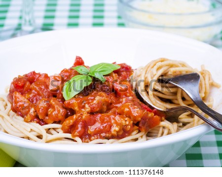 Whole wheat spaghetti dish on table with spoon and fork