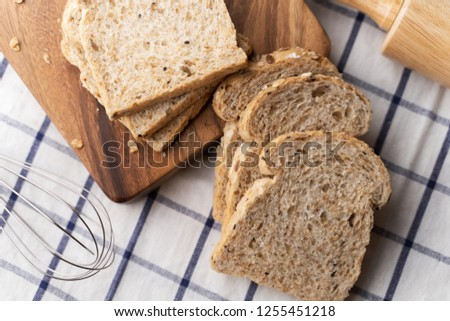 Whole wheat, whole grains bread on dark wooden board, close up, top view #1255451218