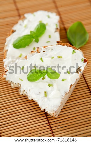 Wholegrain bread with herbal (basil) cream spreading.