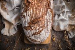 Wholegrain bread with rye stalks and wheat stalks with kitchen cloth overhead arrangement on old wooden table studio shot