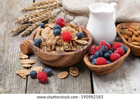 wholegrain flakes with fresh berries, nuts and milk on wooden table, horizontal