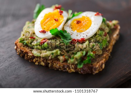 Wholegrain toast bread with guacamole and boiled egg.