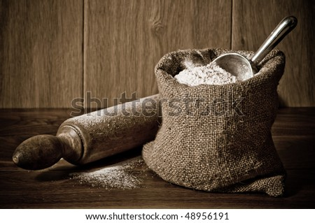 Wholemeal wheat flour in burlap sack with antique rolling pin