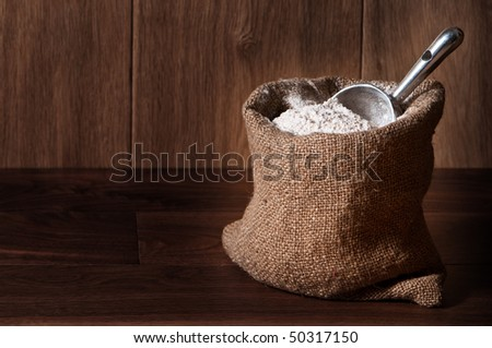 Wholemeal wheat flour in burlap sack with scoop, copy space included