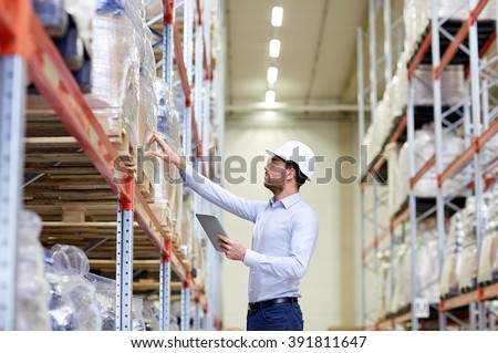 wholesale, logistic, business, export and people concept - man or manager in hardhat with tablet pc computer checking goods at warehouse
