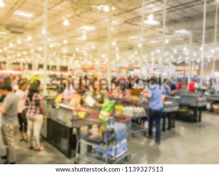 Wholesale shopping, sale, payment, consumerism and people concept. Blurred image cashier with long line of customer at check-out counter of warehouse store in America. Purchase using credit card