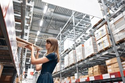 Wholesale warehouse. Beautiful young woman worker of store in shopping center. Girl looking for goods with a tablet is checking inventory levels in a warehouse. Logistics concept