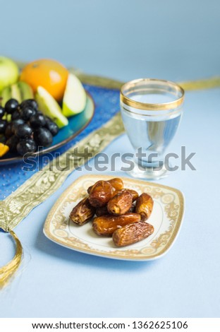 Wholesome, healthy and fat-free food consists of assorted fruits and sweet dates while breaking Ramadan fast. Glass of pure drinking water and dates with fruit plater for Iftar ritual.