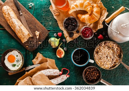 Wholesome rustic breakfast with cereal, fried egg, bread, jams, sausage, milk in a can and coffee spread out on a green wooden background, overhead view