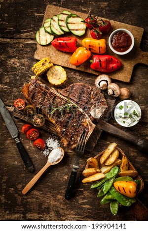 Wholesome spread with t-bone or porterhouse steak served with an assortment of healthy roasted vegetables and savory dips on a rustic wooden table in a country kitchen #199904141