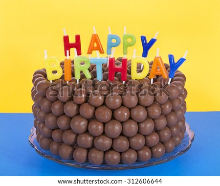 Whopper of a Chocolate Birthday Cake decorated with candy malt balls and Happy Birthday Candles. Blue surface yellow background. Fast and easy home made cake for children or adult birthday party