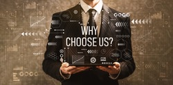 Why choose us with businessman holding a tablet computer on a dark vintage background
