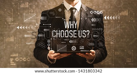 Photo of  Why choose us with businessman holding a tablet computer on a dark vintage background