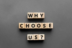 why choose us? - words from wooden blocks with letters, top view gray background