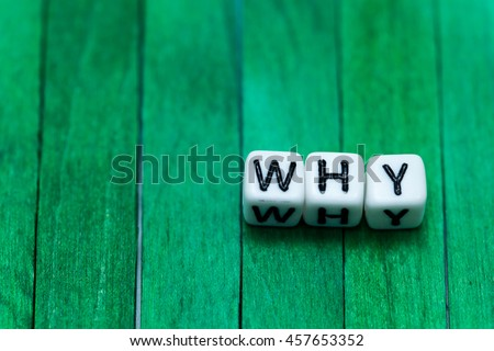 Photo of  WHY cube blocks arranged on green wooden background