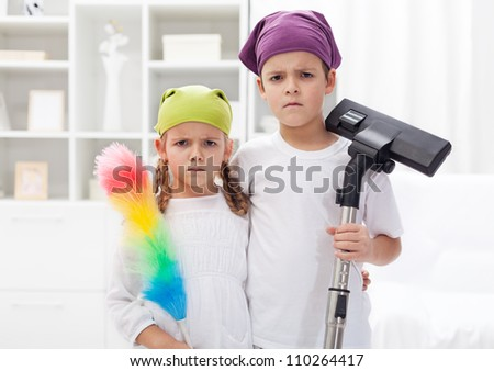 Why do we have to clean our room - upset kids with cleaning utensils - stock photo
