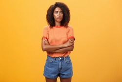 Why life so unfair. Portrait of cute offended and gloomy displeased african american young woman with afro hairstyle sulking pouting crossing arms on chest looking up with envy or jealousy