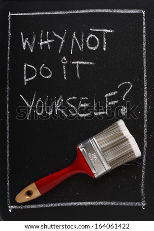 Why Not Do It Yourself written on a used blackboard above a red painting brush as a concept for home decorating and self sufficiency.
