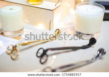 Wick golden, black, silver metal scissors for extinguishing white aroma candles in glass cups are lying on the table. Modern fashionable and comfortable accessory for home. Foto stock ©