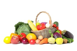 Wicker basket and different vegetables isolated on white background