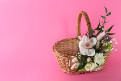 Wicker basket decorated with beautiful flowers on pink background, space for text. Easter item