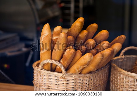 Wicker basket full of baguettes, tasty delicious crusty bread in bakery shopfront