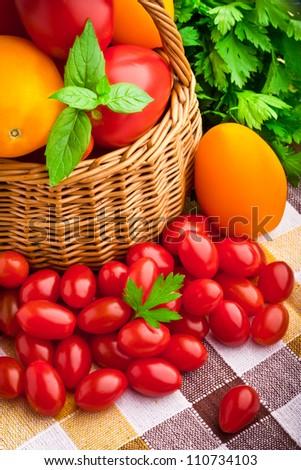 Wicker basket full of fresh tomatoes and cherry tomatoes