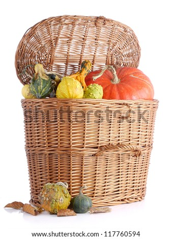 Wicker basket full of summer squashes and pumpkins on white background
