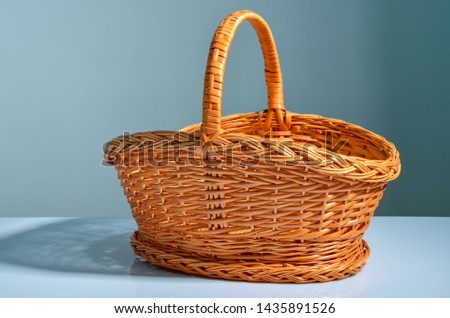 Wicker basket, lighted with soft daylight, is on a white surface. On the background of a turquoise wall Stok fotoğraf ©