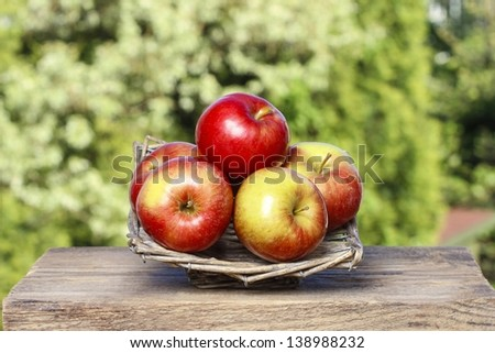 Wicker basket of fresh red ripe apples. Rustic wooden table top in beautiful summer garden on sunny day.  Copy space.