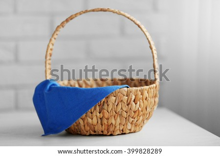 Wicker basket with blue napkin on wooden table, closeup