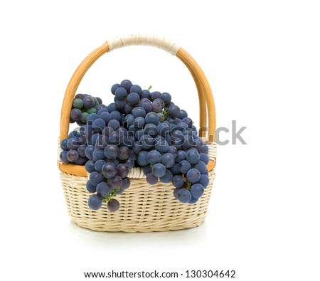 wicker basket with dark grapes on a white background close-up