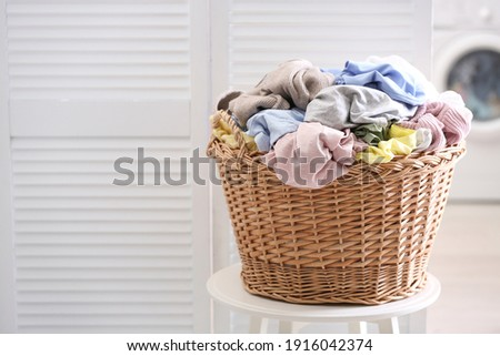 Wicker basket with dirty laundry indoors, space for text