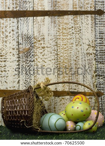 Wicker basket with Easter eggs on grass by old rusted door